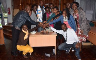 Staff at the FAWE Regional Secretariat in a cake-cutting group photo at Hendrina's farewell party