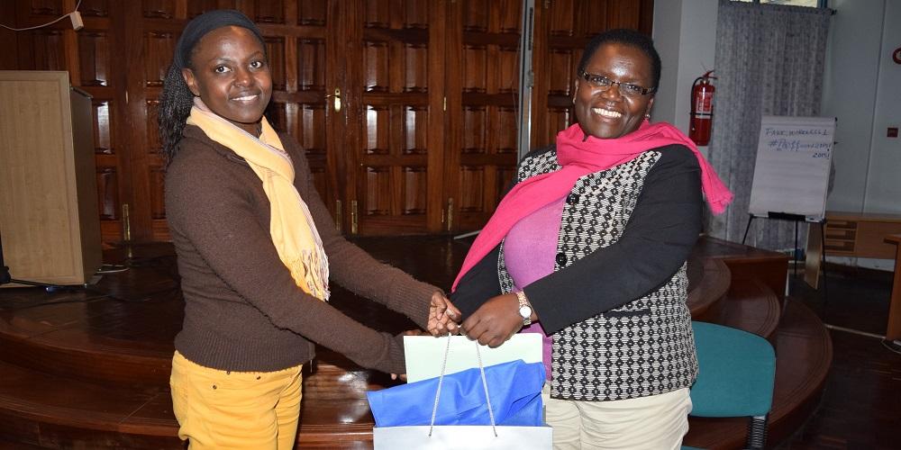 Mme Hendrina Chalwe Doroba, Directrice Exécutive sortante (à droite) est présentée d'un cadeau par la Chargee des Ressources Humaines et d'Administration Mme. Ms. Lilian Nanzala lors de son pot de départ